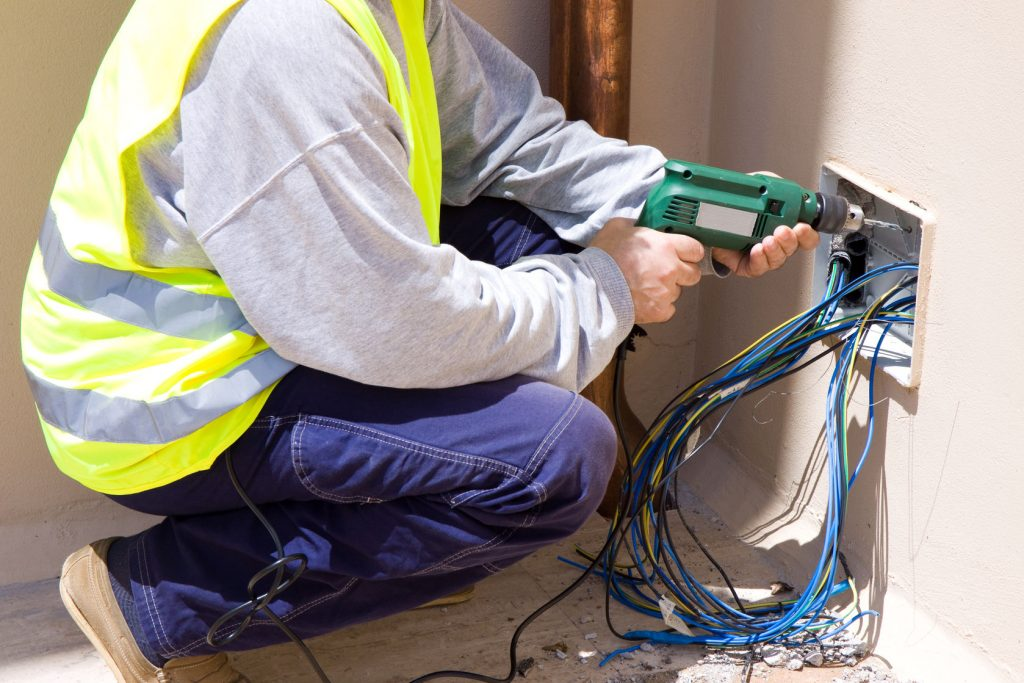 Electrician installing wires into a commercial building
